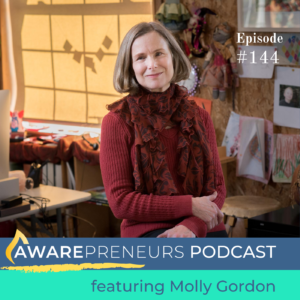 photo of Molly Gordon in a red sweater seated in front of her work station with caption: Awarepreneurs Podcast with Molly Gordon
