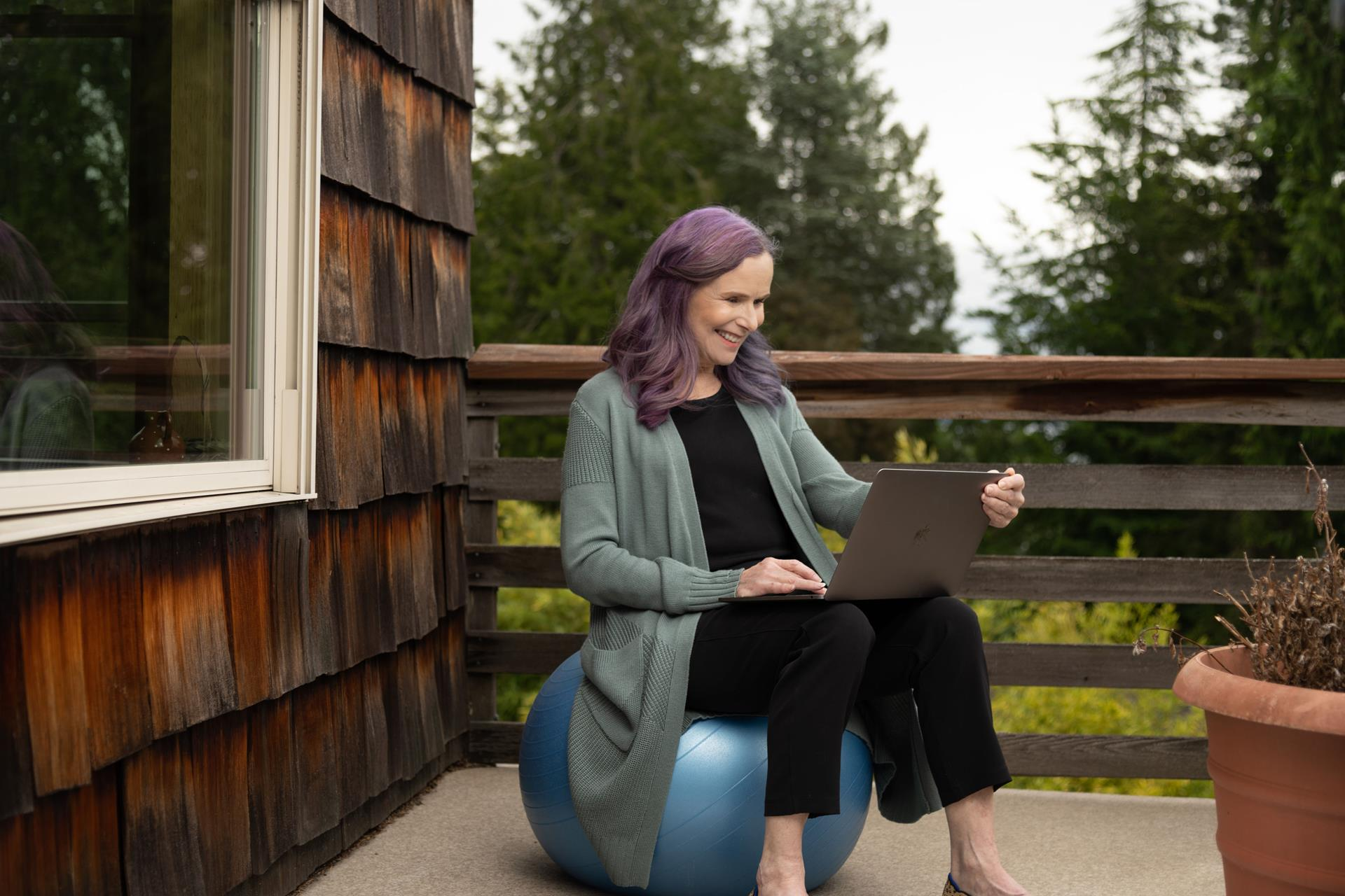 woman with a laptop sitting on a bouncing ball